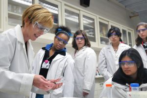 Five diverse women in a science laboratory